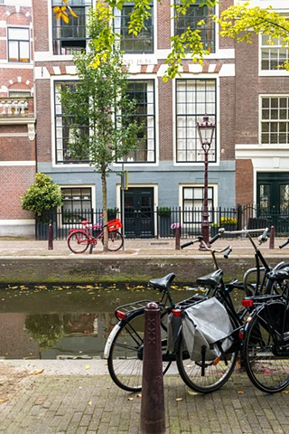 Scene with a red bicycle parked in front of a typical Amsterdam house
