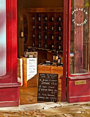 red walls on a St Emilion France wine store, wine crates and bottles on the walls, chalkboard sign