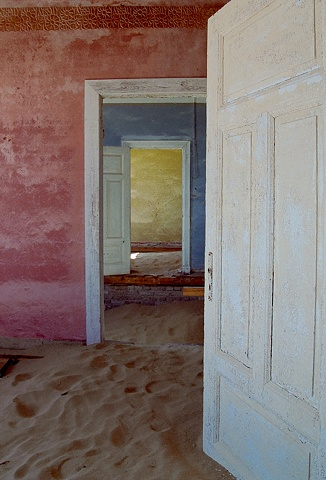 Kolmanskop Namibia, a deserted diamond mining town in the desert, doors aligned to see from the pink room, to the blue room to the yellow room, sand dunes in the house