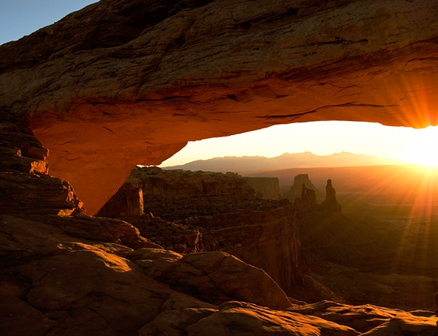 Mesa Arch sunrise, rays of the sun lighting the underside of the rock arch, and washer woman in the background