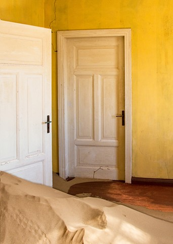 Brilliant yellow and sand coming in through a door in Kolmanskop
