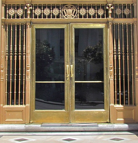 Office building doors in San Francisco, gold colored with street reflections in the glass doors.