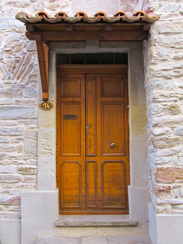 Terra cotta tile awing over a seemingly orange wood door framed by the stone French house.