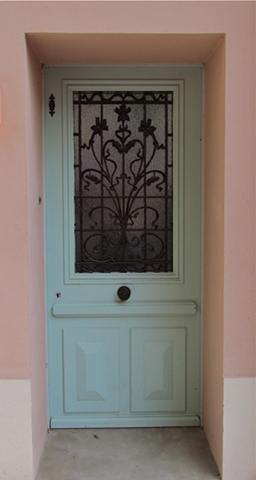 Light mint green doors on pink French house with center handle and black rot iron protecting the glass window.