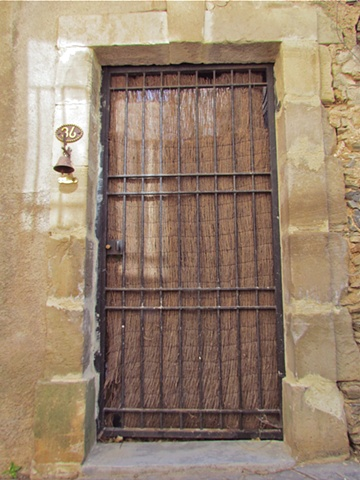 Black rot iron gate, and woven wicker curtain & a wood door on a French stone house.