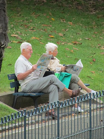 man, woman, Beziers, France, reading, park bench, older, grassy, walkway, wrought iron railing