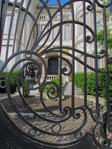 Beziers, gate, wrought iron, black, shutters wall, white, large, house, cobblestone, scroll, double stairs, gold columns, stained glass, planter, shrubs, balcony