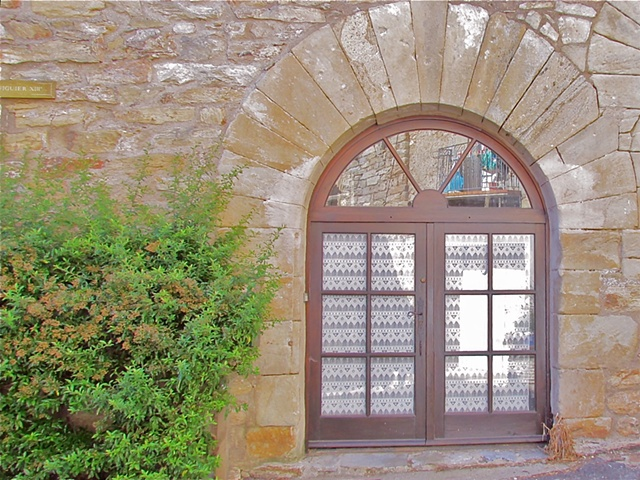 Arched brown wooden doors on French house, framed by stone with white curtains and reflections from other buildings.