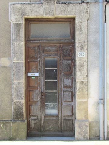Old wooden doors with center glass panel on French home with morter frame.