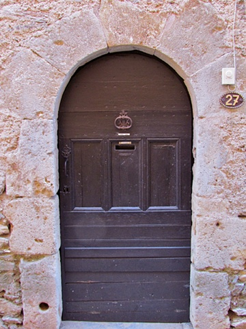 Dark solid wood door on French stone house with brass knocker and mail slot.