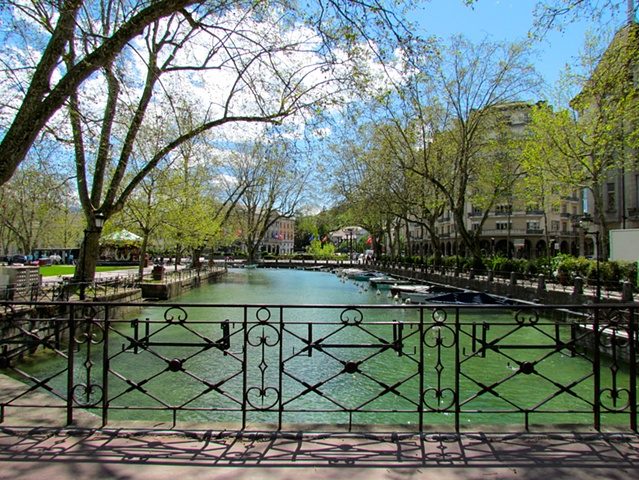 water, bridge, trees, walkway, small boats, blue sky, white clouds. wrought iron rail, shadow, reflections