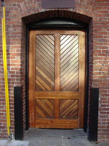 Brick building doors in San Francisco's Mission District, wood frame where doors once were located.
