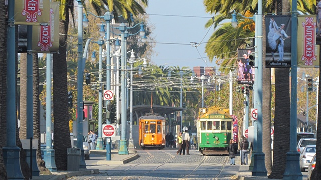 Old streetcars on the embarcadero in San Francisco surrounded by palm trees and people
