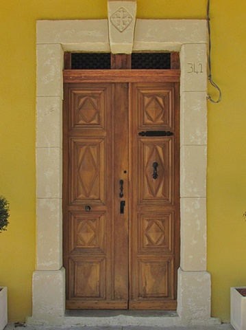 Doors for a French house, medium wood doors on yellow house with interesting frame