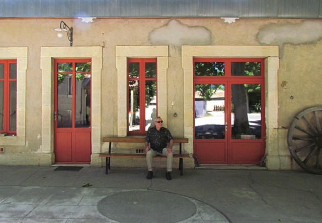 reflections in doors, windows, red framed doors, bench, man, green shirt, sunglasses, sunlight, shadows, wagon wheel, stone building