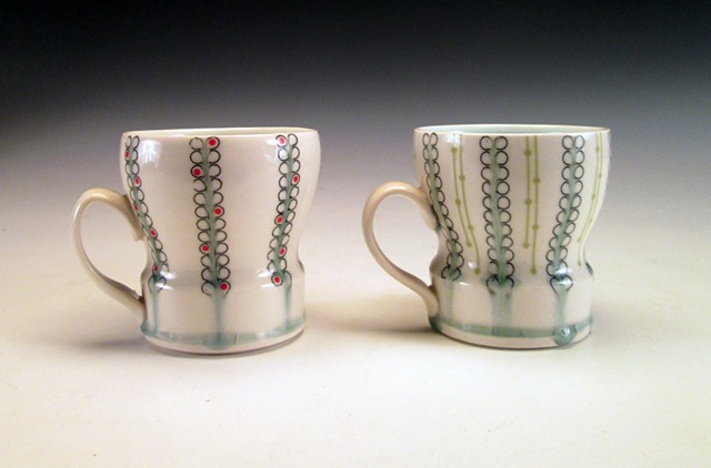 2 thrown porcelain cups with handles with underglaze and overglaze decals
