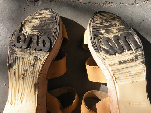 """Carved shoes with the words """"me"""" and """"and"""" on the soles. By Courtney Kessel"""