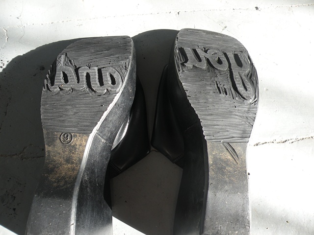 """Carved shoes with the words """"you"""" and """"and"""" on the soles. By Courtney Kessel"""