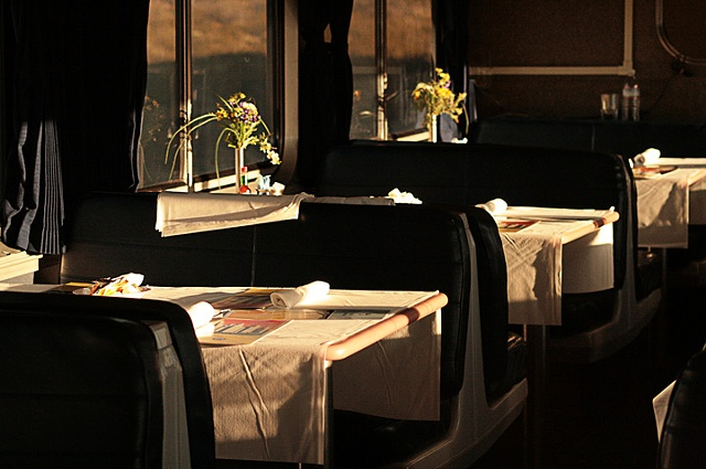 Horizontal beams of sunset invade the quiet elegance of a fully served dining car waiting for the dinner hour..