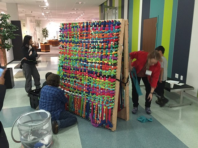 Visitors working on a large weaving during Young Audiences of Western NY's holiday party , 2016