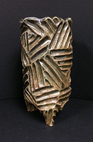 hand carved stoneware vase with geometric pattern under dark moss green glaze