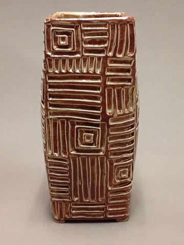 hand carved stoneware vase with geometric pattern under cream-tan glaze