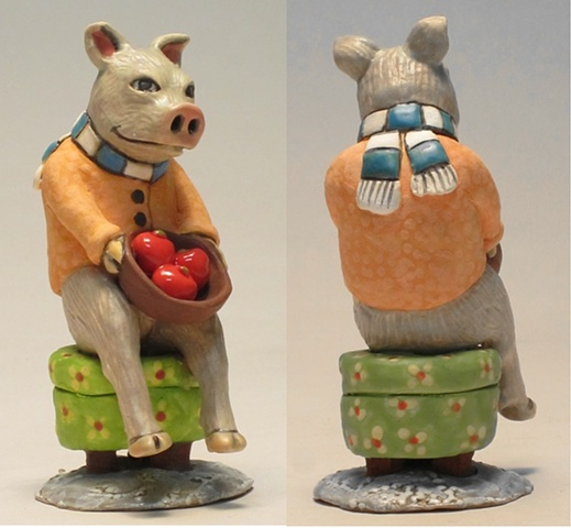 Clay pig on  flowered ottoman.