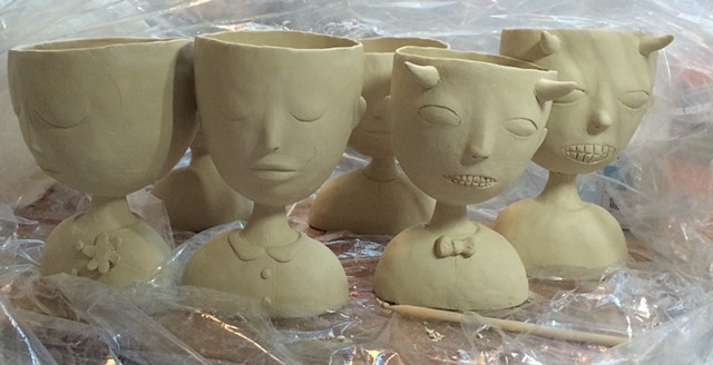 Porcelain people cups before being fired.