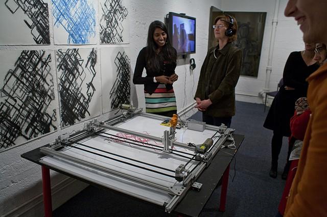 """Santhi Elayaperumal demonstrating """"RedGreenBrain"""" her brainwave-driven robotic drawing machine"""