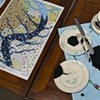 RIVER CAMPAIGN: Detail of hand-painted china, hand-painted flatware and hand-embroidered napkin
