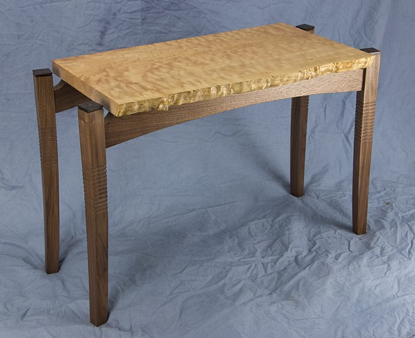 Three quarter view of curly maple and walnut end table