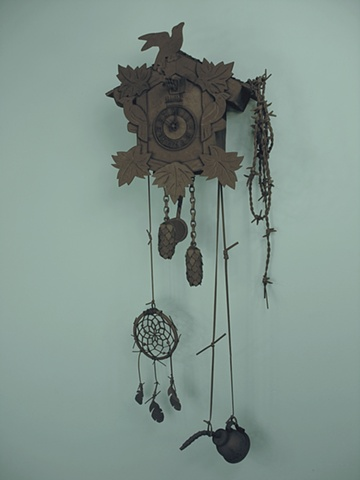 """Black 13""; cuckoo clock, barbed wire, dream catcher, and oil can."