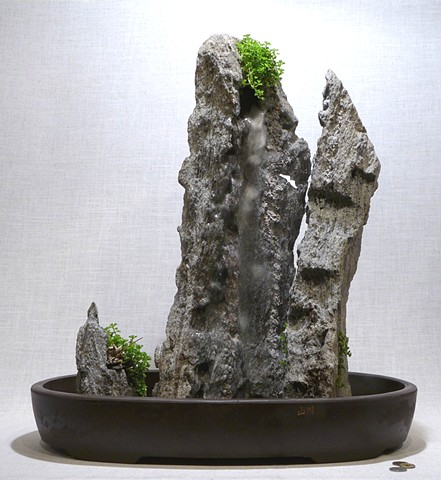 tabletop fountain with feather rock mountains, plants, miniature figures, and fogger