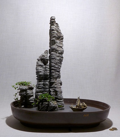 feather rock fountain of volcanic rock towers with mist, plants, and ceramic miniatures