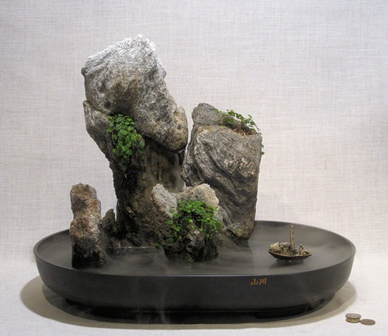 miniature mountain islands with fogger, waterfall, and boat