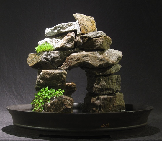 stone arch inuksuk with waterfall and plants