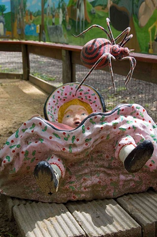 A dirty bottomed Miss Muffet sculpture lying on her back with her skirt up and petticoats showing is  threatened by a spider at a children's petting zoo and amusement park in Michigan photographed by lucy mueller