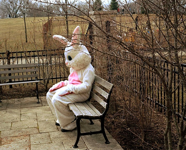Photograph of person in Easter Bunny costume caught in a provate moment looking sad or hungover in a Chicago park photographed by lucy mueller