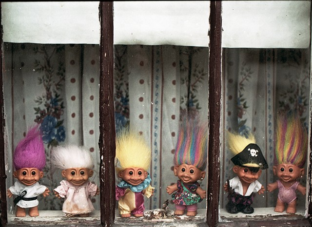 Troll dolls  with brightly colored hair and costumes in the window of a house in Avondale photographed by Lucy Mueller