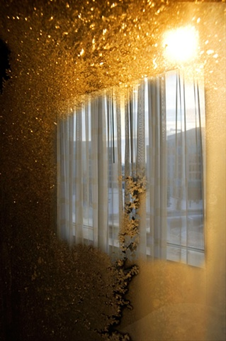 Crystals of frost on a window with harsh sun shining through photographed by Lucy Mueller