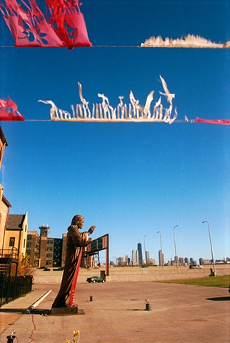 Giant Jesus Statue in a parking lot by Illinois 90/94 in chicago with papel picado or Mexican paper flags in the foreground photographed by Lucy Mueller