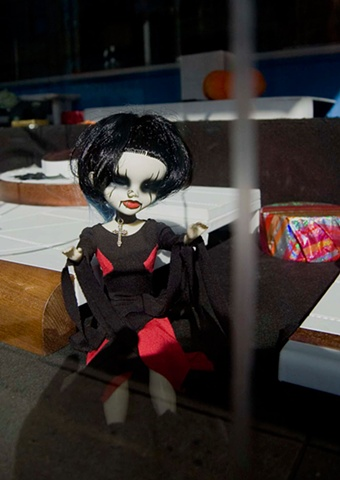 Goth punk doll with black hair and a nose piercing  in the window of a jewelry store on Milwaukee Ave in Chicago photographed by Lucy Mueller