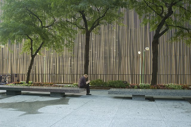 Man sits reading a book in a Michigan Avenue Plaza with the sun setting on a wall behind him that has a digital hum by Lucy Mueller