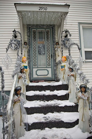 Dark and light skinned Christmas angels line the snow covered steps and porch of a house by Lucy Mueller