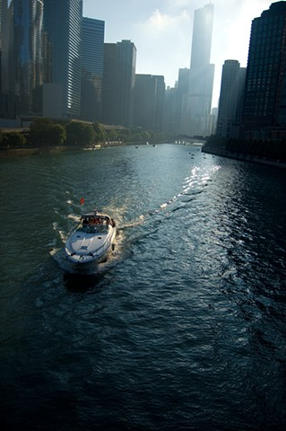 Power boat on the Chicago River surrounded by skyscrapers by lucy Mueller Photography