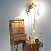 Title/Materials: Chests of Drawers, Lamps, Light Bulbs, Crutches, Surge Protector, Circuit Taps, Artificial Flowers, Paint, Sawdust, Wood Glue, Extension Cord