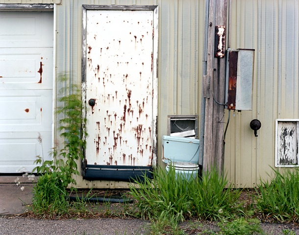 image of rust spotted barn with toilet by a door in grass.