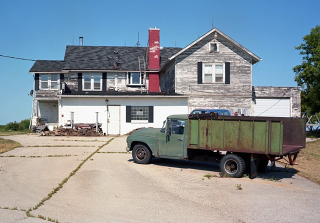 image of a white building with pealing paint, green truck in front with flat tire