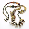 a long rope of shells, pearls, tiger coral, carnelian with a brass toggle