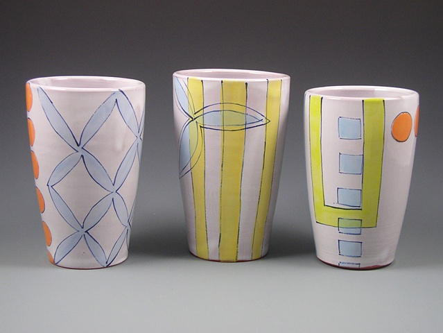 group of thrown terra-cotta tumblers, with handpainted majolica glaze